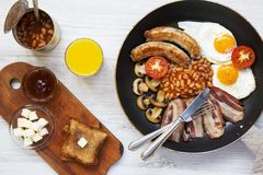 English breakfast in a pan with fried eggs, bacon, sausages, beans and toasts on white wooden background, top view. Flat lay. From above Royalty Free Stock Photos