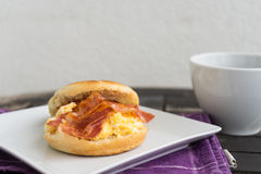 English breakfast. Salt muffin with scrambled eggs, bacon and ch Stock Photography