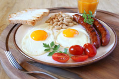 English breakfast with sausage, fried eggs and baked beans Royalty Free Stock Photos