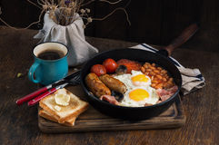 English breakfast with sausages, bacon, fried eggs, beans, toast Stock Photo
