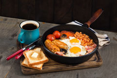 English breakfast with sausages, bacon, fried eggs, beans, toast Stock Photos
