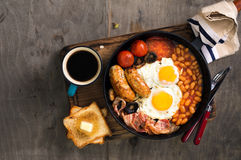English breakfast with sausages, bacon, fried eggs, beans, toast Stock Photography