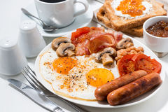English breakfast of scrambled eggs with bacon, sausages Royalty Free Stock Image