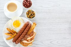 English breakfast with smoked sausages, scrambled eggs, bacon, mushrooms, toast and beans. Tea with milk. Breakfast on a white pla stock photography