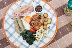 English breakfast on a table with fried egg, baked beans, fried potatoes, bacon, tomato, sausages, mushroom, barbecue sauce, and f Royalty Free Stock Photo