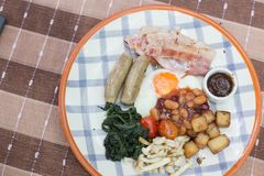 English breakfast on a table with fried egg, baked beans, fried potatoes, bacon, tomato, sausages, mushroom, barbecue sauce, and f Royalty Free Stock Images