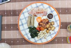 English breakfast on a table with fried egg, baked beans, fried potatoes, bacon, tomato, sausages, mushroom, barbecue sauce, and f stock photo