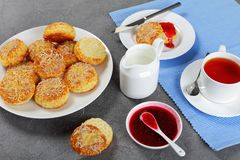 English breakfast with tea and scones. English breakfast - cup of tea served with jug of milk and freshly baked delicious english scones with raspberry jam and Stock Photography