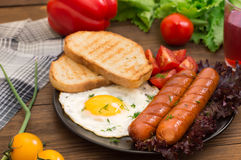 English breakfast - toast, egg, sausages and vegetables salad. Wooden rustic background. Close-up. Top view Stock Image