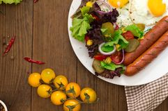 English breakfast - toast, egg, sausages and vegetables salad. Wooden rustic background. Close-up. Top view Royalty Free Stock Images