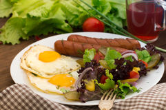 English breakfast - toast, egg, sausages and vegetables salad. Wooden rustic background. Close-up. Top view Stock Photos
