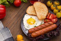 English breakfast - toast, egg, sausages and vegetables salad. Wooden rustic background. Close-up. Top view Stock Photography