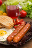 English breakfast - toast, egg, sausages and vegetables salad. Wooden rustic background. Close-up. Top view Royalty Free Stock Photography