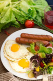 English breakfast - toast, egg, sausages and vegetables salad. Wooden rustic background. Close-up. Top view Royalty Free Stock Image