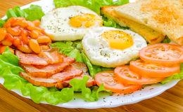 English breakfast. Toast, eggs, bacon, tomatoes, green salad, baked beans Royalty Free Stock Photo