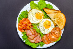 English breakfast. Toast, eggs, bacon, tomatoes, green salad, baked beans Royalty Free Stock Photos