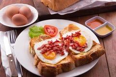 English Breakfast: toast, sunny side up eggs, bacon, ham and salad Royalty Free Stock Photo