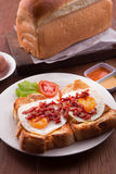 English Breakfast: toast, sunny side up eggs, bacon, ham and salad. With wood base Stock Images