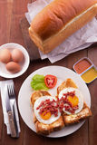 English Breakfast: toast, sunny side up eggs, bacon, ham and salad Royalty Free Stock Photos