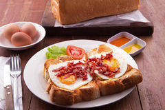 English Breakfast: toast, sunny side up eggs, bacon, ham and salad Royalty Free Stock Photo