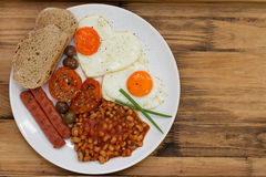 English breakfast on white plate on brown background Stock Photo