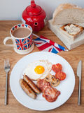 English breakfast on a wooden table top. English breakfast on a wooden table with teapot, cup of tea , toast and a union jack flag Royalty Free Stock Photos