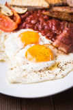 English breakfast (fried eggs, beans, roasted bacon, sausages and vegetables) Royalty Free Stock Photography