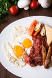English breakfast (fried eggs, beans, roasted bacon, sausages and vegetables) on dark wood background Royalty Free Stock Image