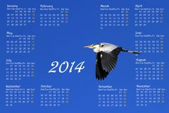 English 2014 calendar with heron in flight. English 2014 calendar with great heron flying across a deep blue sky by sunrise vector illustration