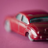 English car toy on fuchsia background. Red toy car with colorful background Royalty Free Stock Photos