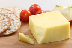 English Cheddar cheese. A wedge of English Cheddar cheese with crackers and cherry tomatoes on a cheeseboard Stock Photos