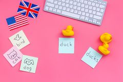English for children. British and american flags, computer keyboard, stickers with vocabulary, toy on pink background. Top view Royalty Free Stock Image