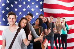 English classes. Group Of Diverse Students Standing In Front Of American Flag Showing Thumb Up Stock Image