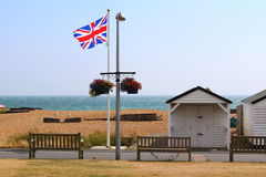 English coast Union Jack flag Kent United Kingdom. View of Deal beach on windy summer day,beach huts,promenade and waving Union Jack flag.Deal is a town in Kent Royalty Free Stock Images