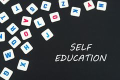 English colored square letters scattered on black background with text keep self education. English school concept, text self education, colored square english Royalty Free Stock Photos