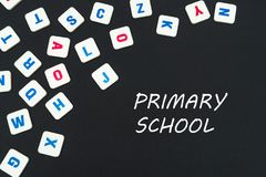 English colored square letters scattered on black background with text primary school. English school concept, text primary school, colored square english Royalty Free Stock Photo