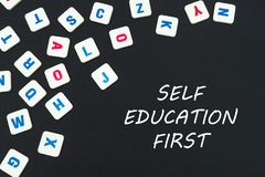 English colored square letters scattered on black background with text self education first. English school concept, text self education first, colored square Stock Photo