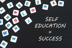 English colored square letters scattered on black background with text self education success. English school concept, text self education success, colored Stock Photos
