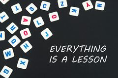 English colored square letters scattered on black background with words everything is a lesson. English language school concept Stock Images
