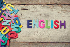 ENGLISH. The colorful words ENGLISH made with wooden letters next to a pile of other letters over old wooden board Royalty Free Stock Images