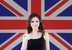 English concept with happy woman student with thumb up against the United Kingdom flag background. Travel and learn english. Language royalty free stock photo