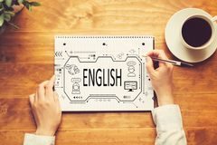 English concept with a person writing in a notebook. On a wooden table royalty free stock photo