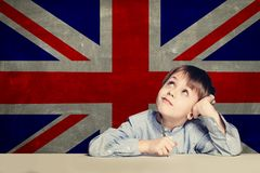 English concept with smart kid student against the UK flag background royalty free stock photo