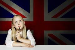 English concept. Thinking child girl student against the UK flag background. Learning English language stock photography