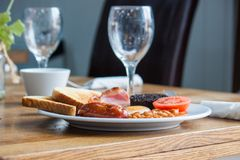 English cooked fried breakfast, 6 items and toast. A greasy fried breakfast of sausage, black pudding, bacon, beans, egg, tomato and toast stock photo