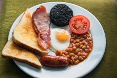 English cooked fried breakfast, 6 items and toast. A greasy fried breakfast of sausage, black pudding, bacon, beans, egg, tomato and toast stock image