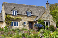English Cotswolds cottage with flowering summer garden. Old traditional English honey golden brown stoned cottage with colourfu flowering front garden on a stock photos