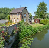 English cottage with colourful cottage garden and wall on the banks of the river Ouse.. Stock Photos