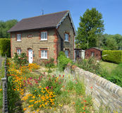English cottage with colourful cottage garden and wall. Royalty Free Stock Photography