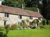 English cottage with flower garden. An English cottage built out of Cotswold stone with stone tiles on the roof, called slates, with a garden full of flowers and Stock Image